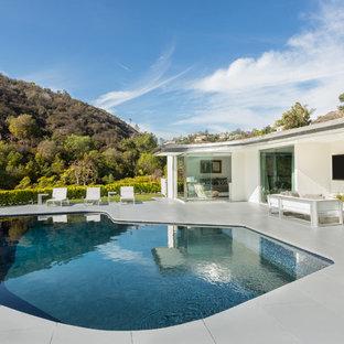 Imagen de piscina retro, tipo riñón, en patio trasero, con losas de hormigón