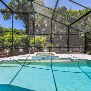 This is an example of a large beach style backyard rectangular pool in Tampa with with privacy feature.