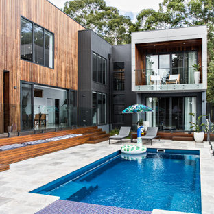 Photo of a large contemporary backyard rectangular pool in Wollongong with a hot tub.