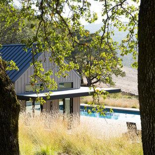 Imagen de casa de la piscina y piscina alargada, campestre, pequeña, rectangular, en patio trasero, con entablado