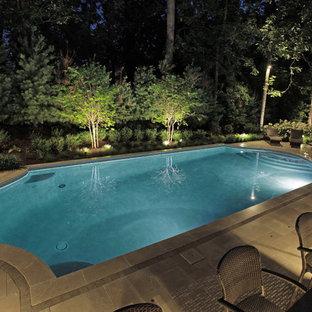 Diseño de piscina alargada, tradicional renovada, extra grande, a medida, en patio trasero, con suelo de baldosas