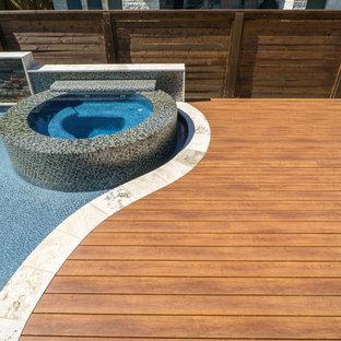 Imagen de piscinas y jacuzzis actuales, de tamaño medio, a medida, en patio trasero, con entablado