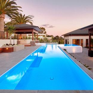 Esempio di una grande piscina monocorsia contemporanea rettangolare dietro casa con una vasca idromassaggio