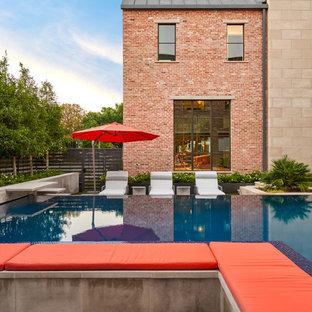 Ejemplo de piscina infinita, tradicional renovada, de tamaño medio, en forma de L, en patio trasero, con losas de hormigón