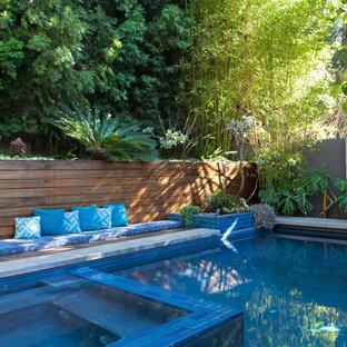 Inspiration pour une grand piscine arrière vintage rectangle avec un bain bouillonnant.