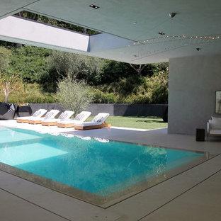 Diseño de piscina infinita, moderna, grande, rectangular, en patio trasero, con adoquines de hormigón