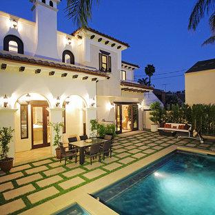 Mittelgroßer Mediterraner Pool hinter dem Haus in rechteckiger Form mit Wasserspiel und Natursteinplatten in Los Angeles