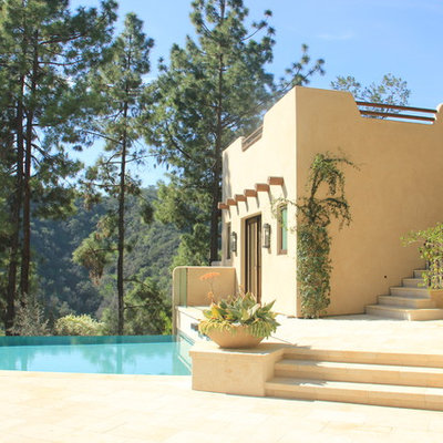 Inspiration for a large southwestern side yard custom-shaped and stone infinity pool house remodel in Los Angeles