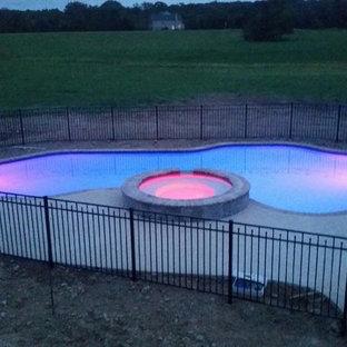 Foto de piscina con fuente de tamaño medio, a medida, en patio trasero, con adoquines de hormigón