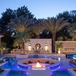 Inspiration for a large modern back custom shaped swimming pool in Tampa with natural stone paving.