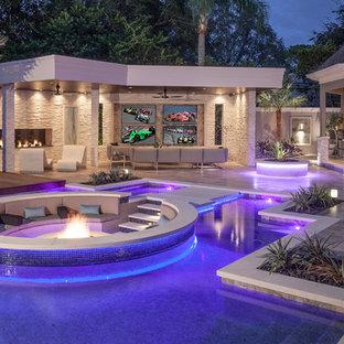 Idee per una grande piscina moderna personalizzata dietro casa con pavimentazioni in pietra naturale e una dépendance a bordo piscina