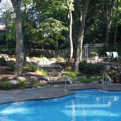 Mid-sized arts and crafts courtyard stamped concrete and custom-shaped aboveground pool photo in Detroit