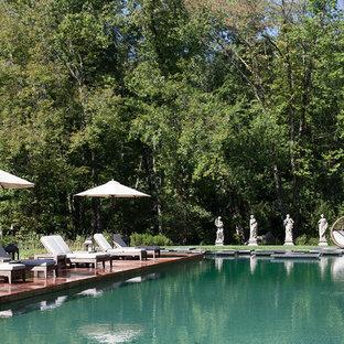 Ejemplo de piscina con fuente natural, clásica renovada, grande, rectangular, en patio trasero, con adoquines de piedra natural