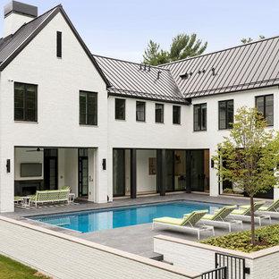 Ejemplo de piscina moderna, extra grande, rectangular, en patio trasero, con adoquines de piedra natural