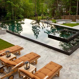 Ejemplo de piscinas y jacuzzis infinitos, actuales, grandes, rectangulares, en patio trasero, con adoquines de piedra natural
