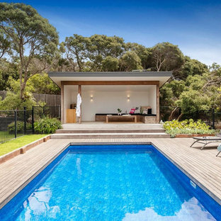 This is an example of a beach style backyard rectangular lap pool in Melbourne with a pool house and decking.