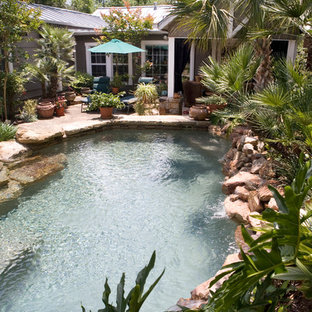 This is an example of a small country backyard custom-shaped natural pool in Austin with natural stone pavers.