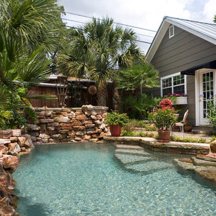 Small country backyard custom-shaped natural pool in Austin with natural stone pavers and a hot tub.
