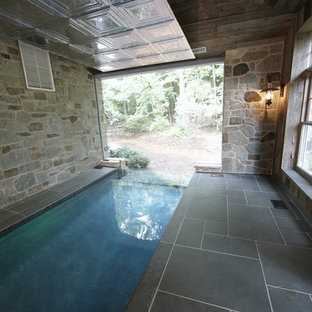 This is an example of a mid-sized country rectangular infinity pool in Milwaukee with tile.