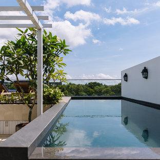 Esempio di una piscina fuori terra etnica rettangolare sul tetto con piastrelle