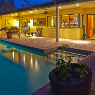 Example of a large eclectic backyard brick and rectangular lap hot tub design in Miami