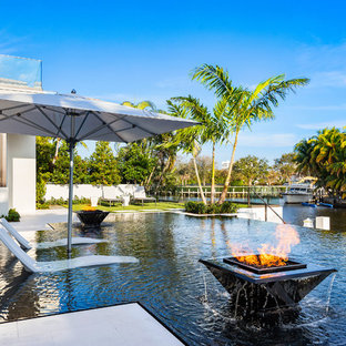 Large minimalist backyard tile and rectangular infinity pool fountain photo in Miami