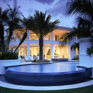 Foto de piscinas y jacuzzis infinitos, contemporáneos, grandes, a medida, en patio trasero, con adoquines de piedra natural