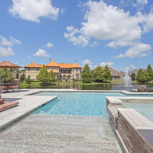 This is an example of a large transitional backyard pool in New Orleans with a hot tub.