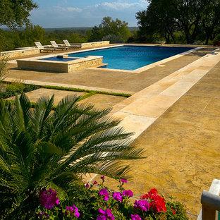 Modelo de piscina alargada, clásica, extra grande, rectangular, en patio trasero, con losas de hormigón