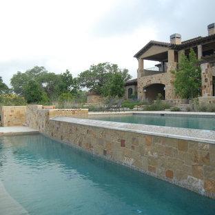 Modelo de piscina con fuente alargada, clásica, extra grande, rectangular, en patio trasero, con losas de hormigón