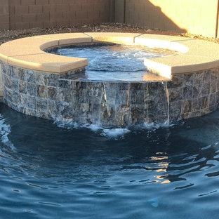 Ejemplo de piscinas y jacuzzis alargados, minimalistas, de tamaño medio, tipo riñón, en patio trasero, con adoquines de hormigón