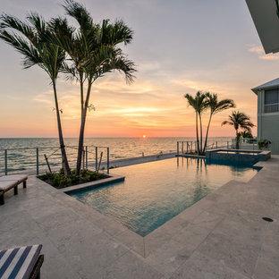 Ispirazione per una grande piscina a sfioro infinito contemporanea personalizzata dietro casa con una vasca idromassaggio e pavimentazioni in cemento