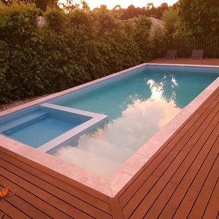 Immagine di una piscina contemporanea rettangolare di medie dimensioni e dietro casa con pedane
