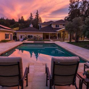 Ispirazione per una grande piscina chic rettangolare dietro casa con una vasca idromassaggio e piastrelle