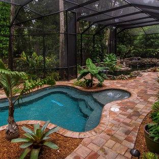 Foto de piscina con fuente natural, tropical, grande, a medida, en patio trasero, con adoquines de ladrillo