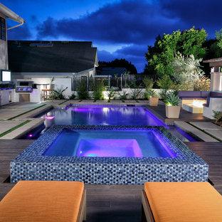 Diseño de piscina con fuente natural, actual, de tamaño medio, rectangular, en patio trasero, con suelo de baldosas