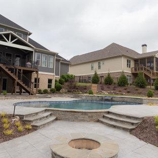 Imagen de piscinas y jacuzzis naturales, clásicos, de tamaño medio, a medida, en patio trasero, con losas de hormigón