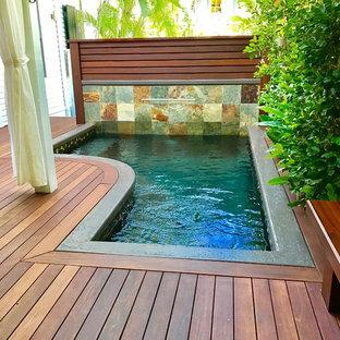Imagen de piscina con fuente tropical, pequeña, en forma de L, en patio trasero, con entablado