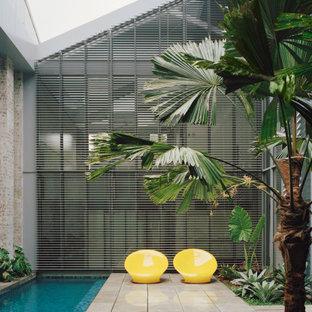 Ejemplo de piscina alargada, urbana, rectangular, con suelo de baldosas