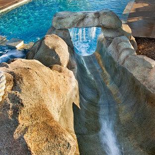 Ejemplo de piscina con tobogán tropical, de tamaño medio, rectangular, en patio trasero, con losas de hormigón