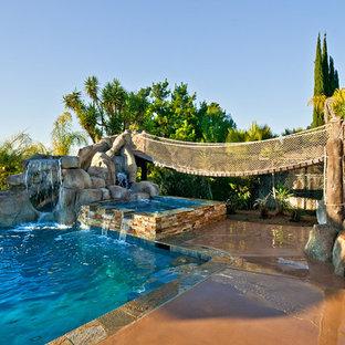 Foto de piscina con tobogán alargada, tropical, de tamaño medio, rectangular, en patio trasero, con losas de hormigón