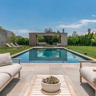 Inspiration för stora moderna rektangulär pooler på baksidan av huset, med naturstensplattor