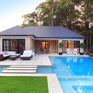Design ideas for a large transitional backyard custom-shaped pool in Brisbane with a pool house and tile.