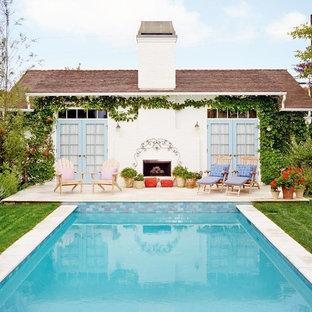 Создайте стильный интерьер: прямоугольный бассейн среднего размера на заднем дворе в стиле шебби-шик с домиком у бассейна и мощением тротуарной плиткой - последний тренд