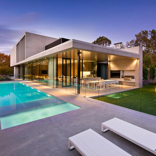 Photo of a large modern backyard rectangular lap pool in Melbourne with concrete slab and a hot tub.