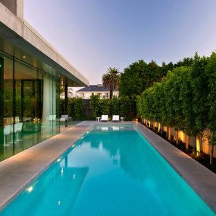 Imagen de piscinas y jacuzzis alargados, minimalistas, grandes, rectangulares, en patio trasero, con losas de hormigón