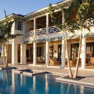 Photo of a tropical backyard custom-shaped pool in Miami.