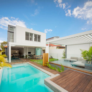 Photo of a contemporary backyard custom-shaped pool in Sydney with decking.