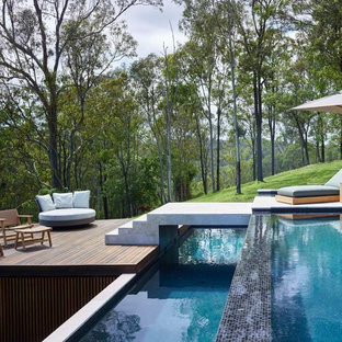 Modern backyard rectangular infinity pool in Brisbane with decking.
