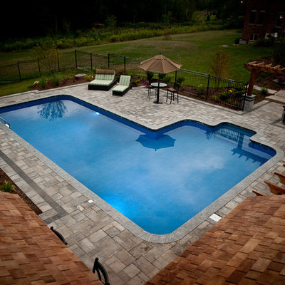 Mid-sized arts and crafts backyard concrete paver and rectangular natural pool house photo in Toronto